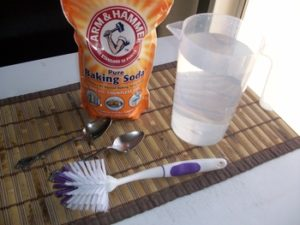 How To Clean an Enameled Cast Iron Dutch Oven - Picture of 2 Tablespoons of Baking Soda 2-quarts hot water and Dish scrubber
