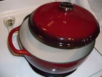 5 Reasons To Own An Enameled Cast Iron Dutch Oven - Picture of red Enameled Cast Iron Dutch Oven with lid on white stove