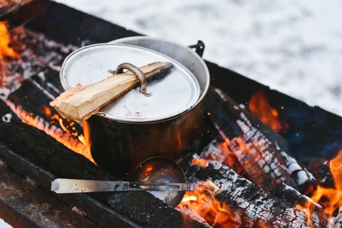 How-To-Clean-A-Cast-Iron-Dutch-Oven - picture of Dutch oven cooking over wood fire